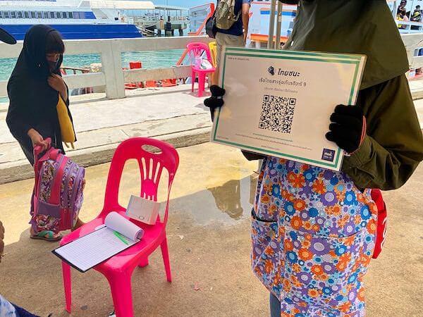 バリハイ桟橋のラン島行きフェリー乗り場前でタイチャナのQRコードを掲げているスタッフ